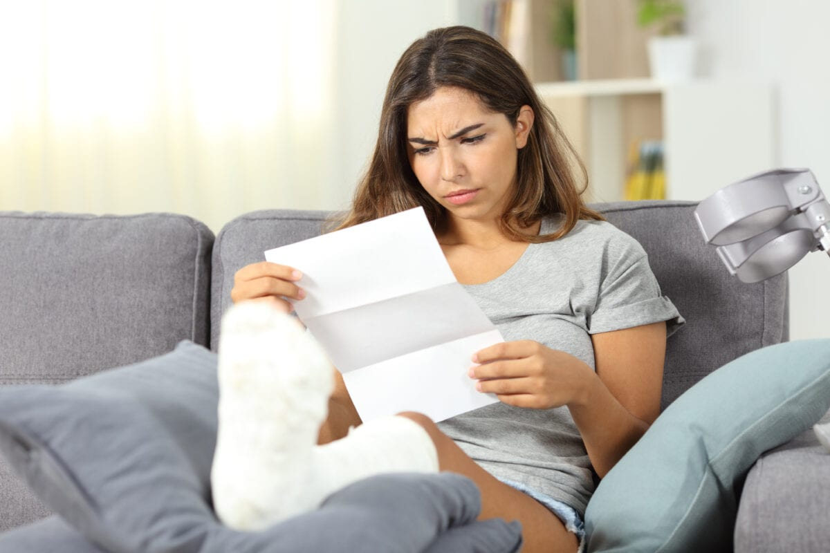 Worried injured woman reading a letter sitting on a couch in the living room at home after being denied workers comp claims